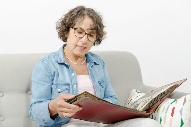 Mulher de meia idade, olhando para o álbum de fotos