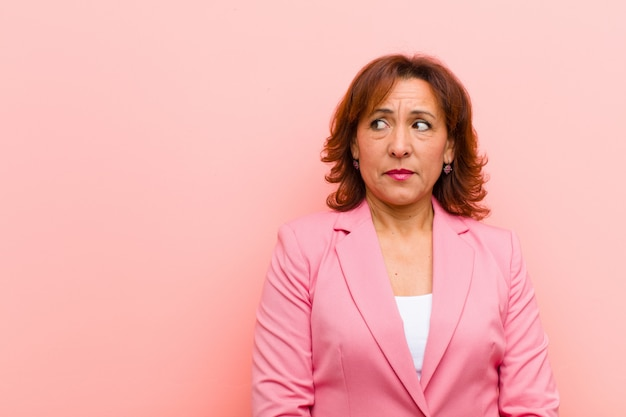 Mulher de meia idade olhando preocupado, estressado, ansioso e assustado, em pânico e cerrando os dentes contra a parede rosa