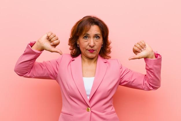 Mulher de meia idade, olhando triste, decepcionado ou com raiva, mostrando os polegares para baixo em desacordo, sentindo-se frustrado contra a parede rosa