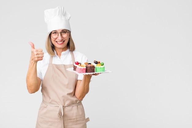 Mulher de meia idade padeiro com bolos na parede do espaço de cópia