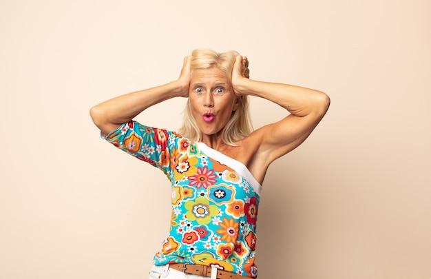 Mulher de meia-idade parecendo animada e surpresa, boquiaberta e com as duas mãos na cabeça, sentindo-se uma sortuda vencedora