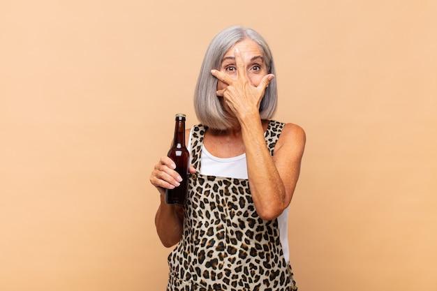 Mulher de meia-idade parecendo chocada, assustada ou apavorada, cobrindo o rosto com a mão e espiando por entre os dedos com uma cerveja
