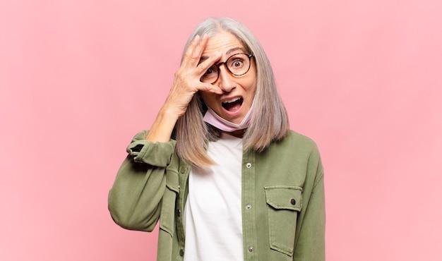 Mulher de meia-idade parecendo chocada, assustada ou apavorada, cobrindo o rosto com a mão e espiando por entre os dedos