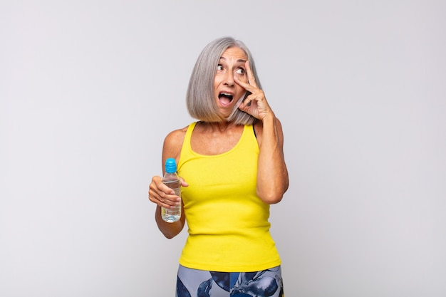 Mulher de meia-idade parecendo chocada, assustada ou apavorada, cobrindo o rosto com a mão e espiando por entre os dedos.