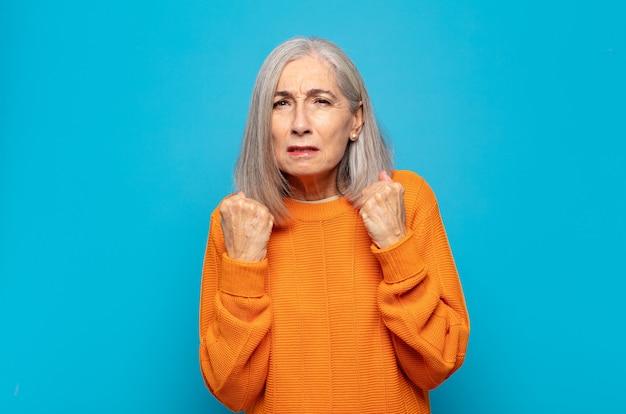 Mulher de meia-idade parecendo confiante, irritada, forte e agressiva, com punhos prontos para lutar em posição de boxe