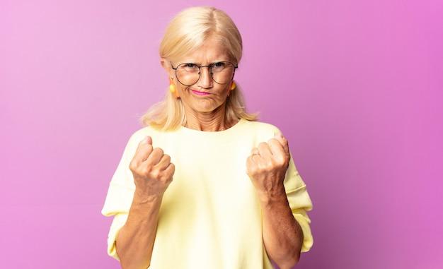 Mulher de meia-idade parecendo confiante, zangada, forte e agressiva, com punhos prontos para lutar em posição de boxe
