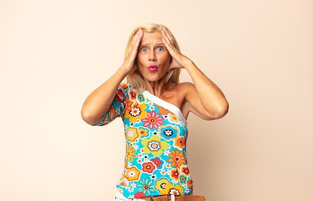 Mulher de meia-idade parecendo desagradavelmente chocada, assustada ou preocupada, com a boca bem aberta e cobrindo as duas orelhas com as mãos