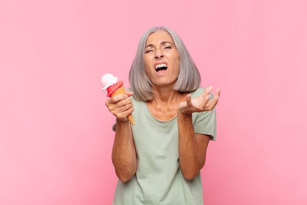 Mulher de meia-idade parecendo desesperada e frustrada, estressada, infeliz e irritada, gritando e gritando tomando um sorvete