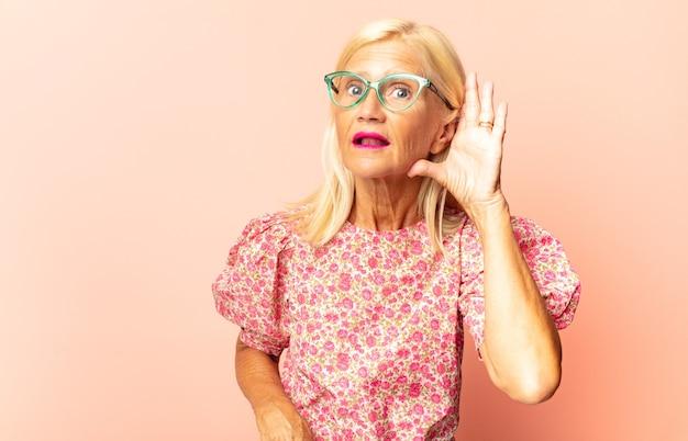 Mulher de meia-idade parecendo desnorteada e atônita, com a mão na testa olhando para longe, observando ou procurando