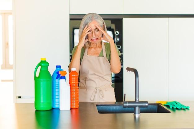 Mulher de meia-idade parecendo estressada e frustrada, trabalhando sob pressão, com dor de cabeça e preocupada com problemas