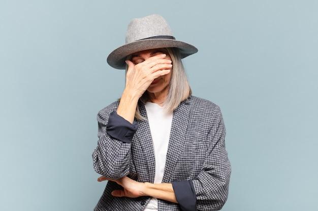 Mulher de meia-idade parecendo estressada, envergonhada ou chateada, com dor de cabeça, cobrindo o rosto com a mão