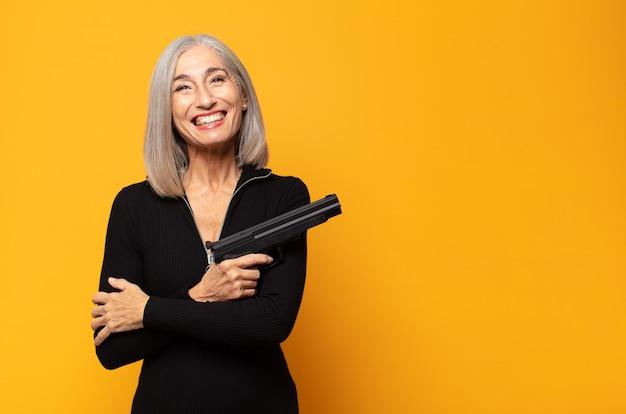 Mulher de meia-idade parecendo feliz e agradavelmente surpresa, animada com uma expressão de fascínio e choque