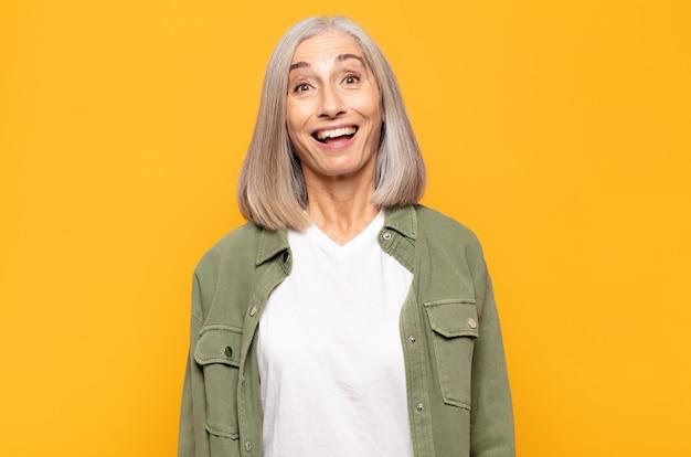 Mulher de meia-idade parecendo feliz e agradavelmente surpresa, animada com uma expressão fascinada e chocada