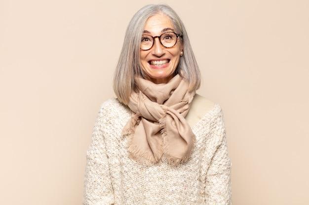 Mulher de meia-idade parecendo feliz e boba com uma ampla