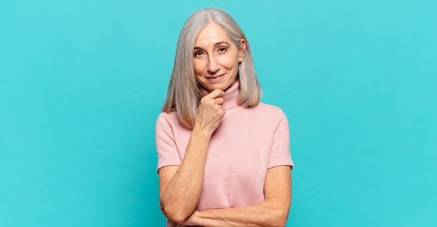 Mulher de meia-idade parecendo feliz e sorrindo com a mão no queixo, pensando ou fazendo uma pergunta, comparando opções