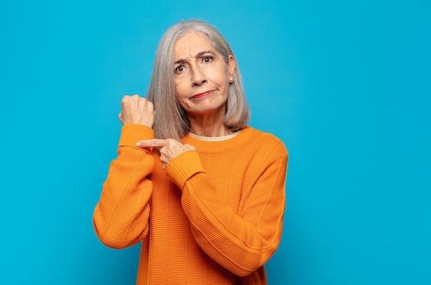 Mulher de meia-idade parecendo impaciente e zangada, apontando para o relógio, pedindo pontualidade, quer chegar na hora