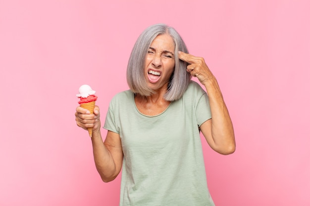 Mulher de meia-idade parecendo infeliz e estressada, gesto suicida fazendo sinal de arma com a mão, apontando para a cabeça tomando um sorvete