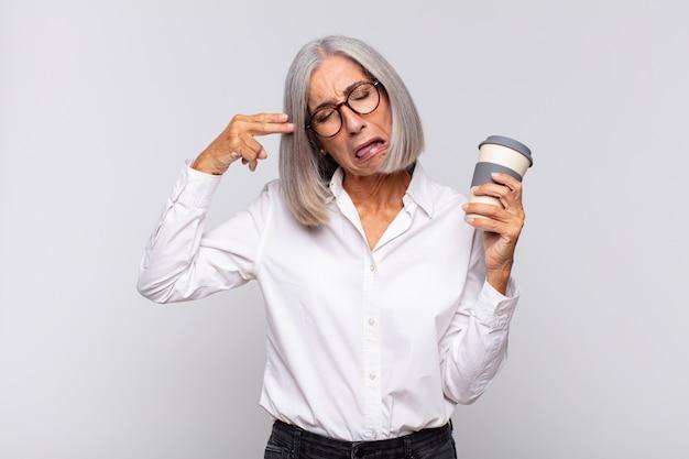 Mulher de meia-idade parecendo infeliz e estressada, gesto suicida fazendo sinal de arma com a mão