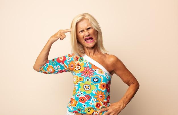 Mulher de meia-idade parecendo infeliz e estressada, gesto suicida isolado