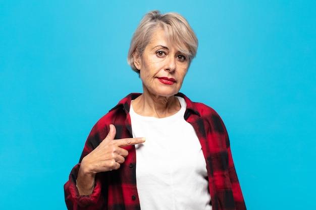Mulher de meia-idade parecendo orgulhosa, confiante e feliz, sorrindo e apontando para si mesma ou fazendo o primeiro sinal