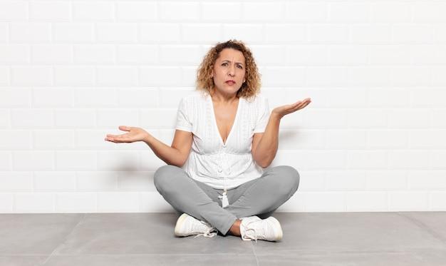 Mulher de meia idade parecendo perplexa, confusa e estressada, pensando entre as diferentes opções, sentindo-se insegura