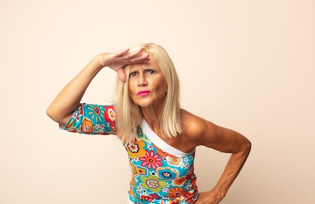 Mulher de meia idade parecendo perplexa e atônita, com a mão na testa olhando para longe, observando ou procurando