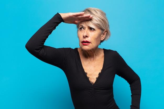 Mulher de meia-idade parecendo perplexa e atônita, com a mão na testa olhando para longe, observando ou procurando