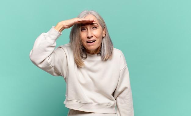 Mulher de meia-idade parecendo perplexa e atônita, com a mão sobre a testa olhando para longe, observando ou procurando