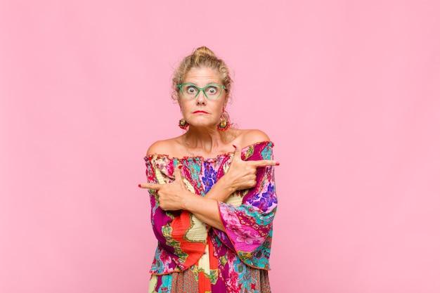 Mulher de meia-idade parecendo perplexa e confusa, insegura e apontando em direções opostas com dúvidas