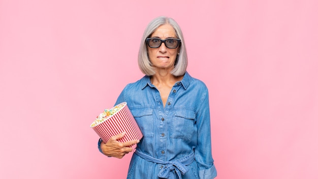 Mulher de meia-idade parecendo perplexa e confusa, mordendo o lábio com um gesto nervoso, sem saber a resposta para o conceito do filme problemático