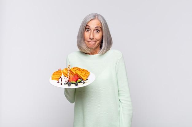 Mulher de meia-idade parecendo perplexa e confusa, mordendo o lábio com um gesto nervoso, sem saber a resposta para o problema. conceito de café da manhã