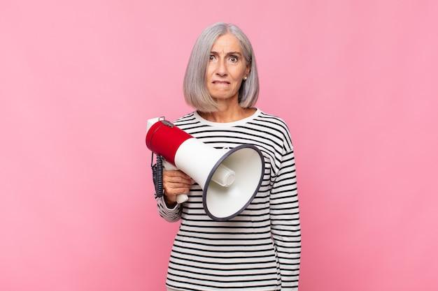 Mulher de meia-idade parecendo perplexa e confusa, mordendo o lábio com um gesto nervoso, sem saber a resposta para o problema do megafone