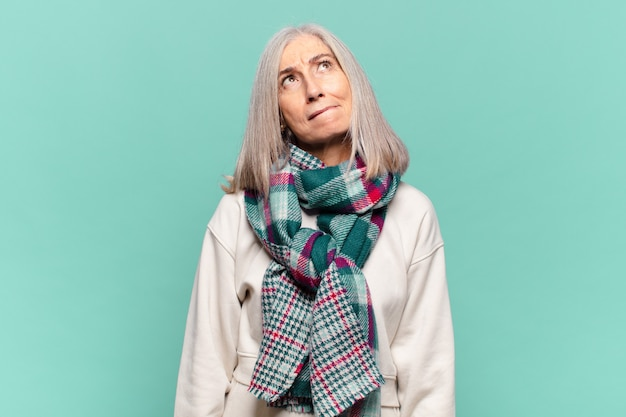 Mulher de meia-idade parecendo perplexa e confusa, pensando ou tentando resolver um problema ou pensando
