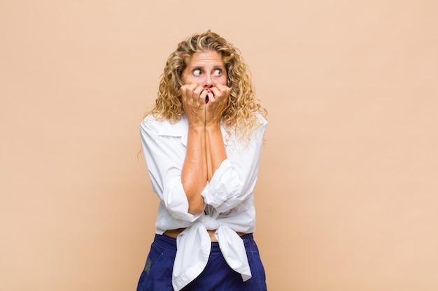 Mulher de meia-idade parecendo preocupada, ansiosa, estressada e com medo, roendo as unhas e olhando para o espaço da cópia lateral