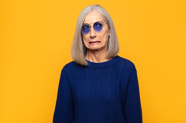 Mulher de meia-idade parecendo preocupada, estressada, ansiosa e assustada, em pânico e cerrando os dentes