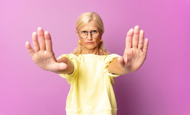 Mulher de meia-idade parecendo séria, infeliz, irritada e descontente isolada