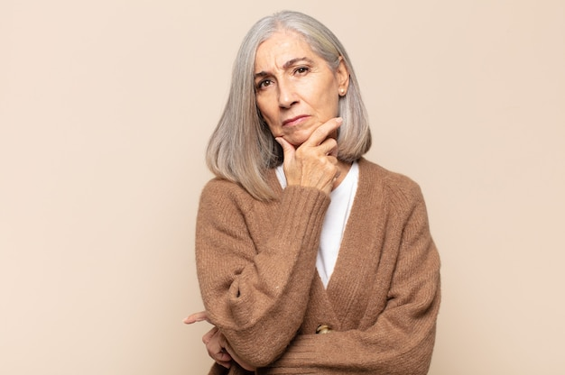 Mulher de meia-idade parecendo séria, pensativa e desconfiada, com um braço cruzado e a mão no queixo, opções de peso