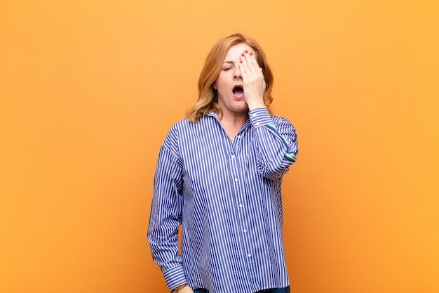 Mulher de meia-idade parecendo sonolenta, entediada e bocejando, com dor de cabeça e uma das mãos cobrindo metade do rosto