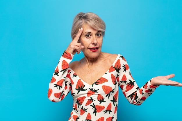 Mulher de meia-idade parecendo surpresa, boquiaberta, chocada, percebendo um novo pensamento, ideia ou conceito