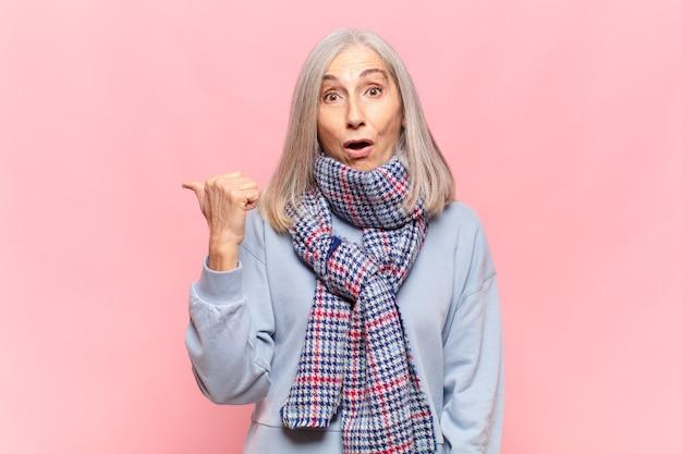 Mulher de meia-idade parecendo surpresa em descrença, apontando para um objeto ao lado e dizendo uau, inacreditável