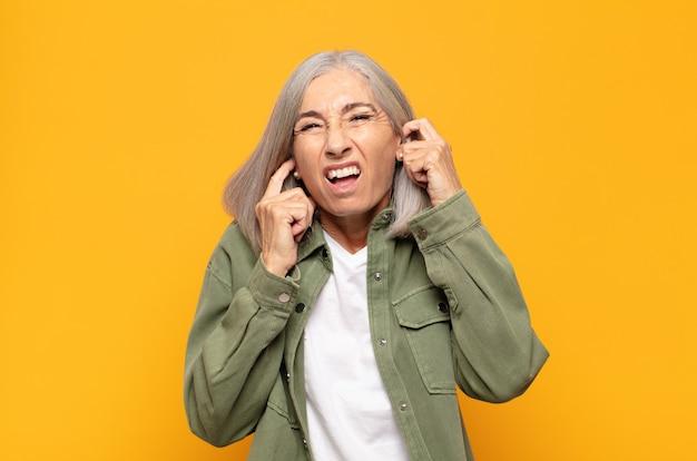 Mulher de meia-idade parecendo zangada, estressada e irritada, cobrindo ambos os ouvidos para um barulho, som ou música alta ensurdecedores