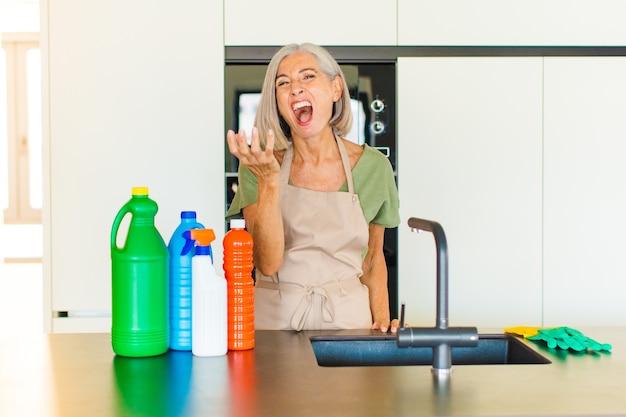 Mulher de meia-idade parecendo zangada, irritada e frustrada gritando wtf ou o que há de errado com você