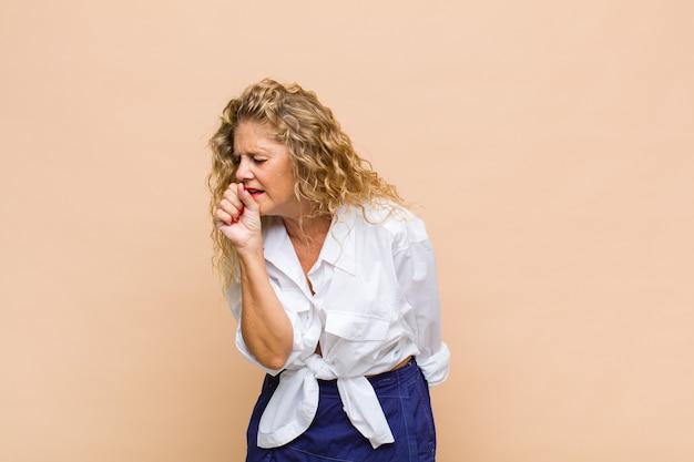 Mulher de meia-idade passando mal com dor de garganta e sintomas de gripe, tosse com a boca coberta