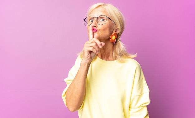 Mulher de meia-idade pedindo silêncio e silêncio, gesticulando com o dedo na frente da boca, dizendo shh ou guardando segredo
