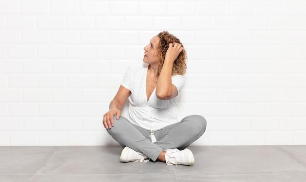 Mulher de meia-idade pensando ou duvidando, coçando a cabeça, sentindo-se perplexa e confusa, visão traseira ou traseira