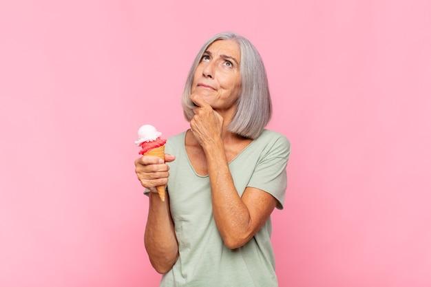Mulher de meia-idade pensando, se sentindo duvidosa e confusa, com opções diferentes, se perguntando qual decisão tomar tomando um sorvete