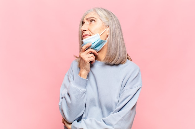 Mulher de meia-idade pensando, sentindo-se duvidosa e confusa, com diferentes opções, imaginando qual decisão tomar