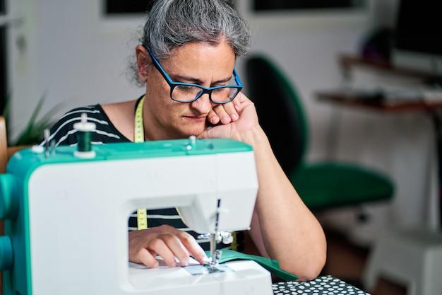 Mulher de meia-idade pensativa, com cabelos brancos, costura na máquina de costura em casa.