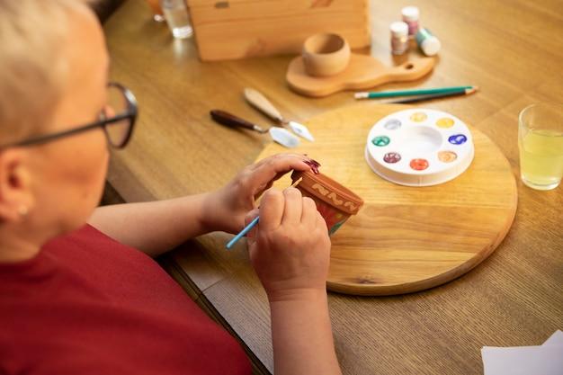 Mulher de meia-idade pinta um vaso de flores em um estúdio caseiro de arte