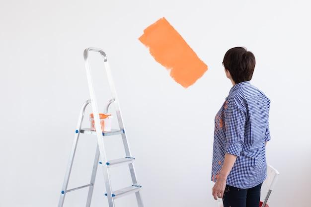 Mulher de meia-idade pintando as paredes da nova casa. conceito de renovação, reparação e redecoração.